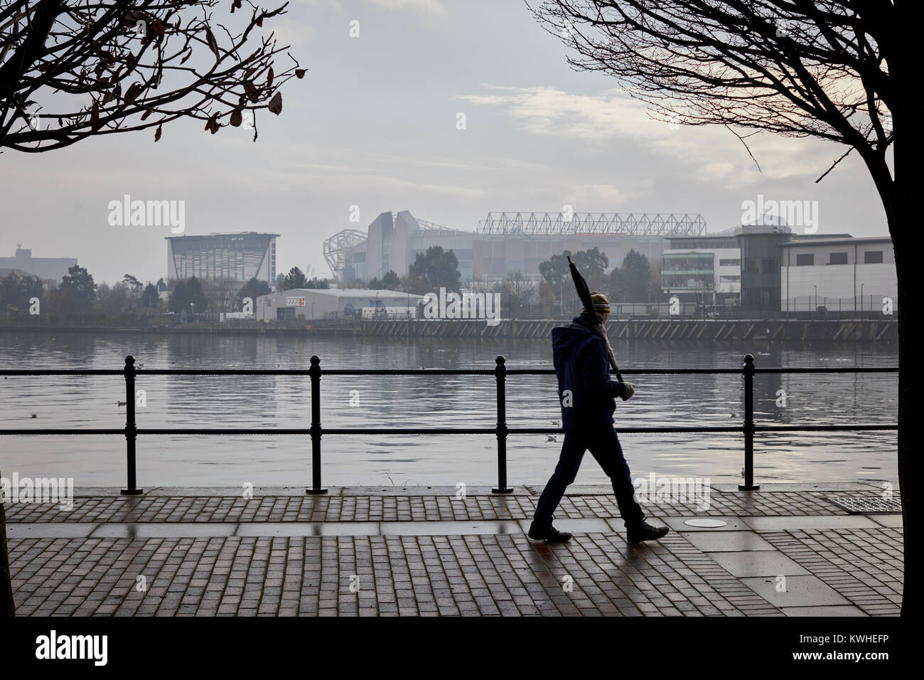 A dull , wet, foggy day Old Trafford stadium, home of Manchester United Football Club seen across the Ship Canal - Stock Image