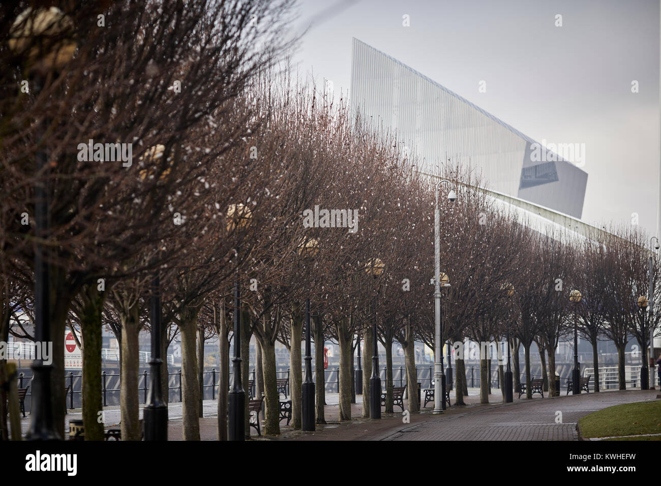 Winter at Trafford Park's Imperial War Museum North (IWM North) seen over the tree lined Salford Quays by architect - Stock Image