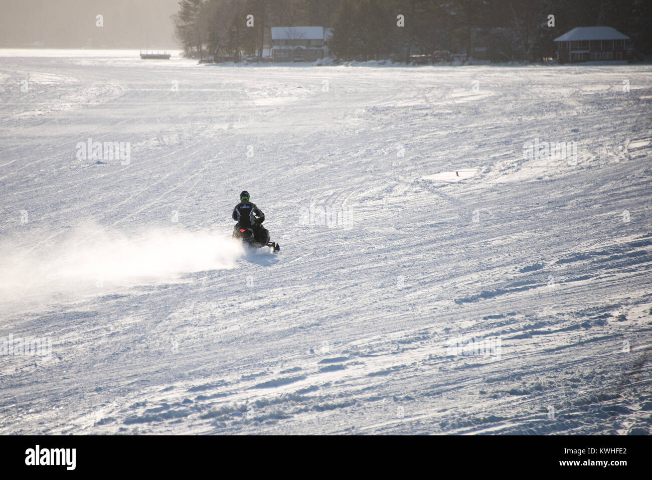 Snowmobile racing across a snow covered frozen Lake Pleasant in the Adirondack Mountains, NY USA stirring up a cloud - Stock Image