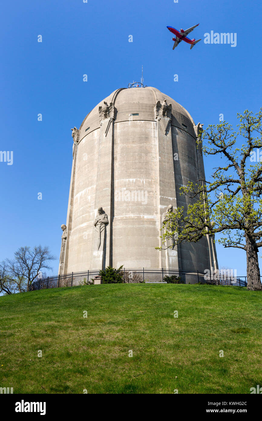 An airplane flying over the 1932 art deco Washburn Park Water tower in South Minneapolis, Minnesota.  The concrete - Stock Image
