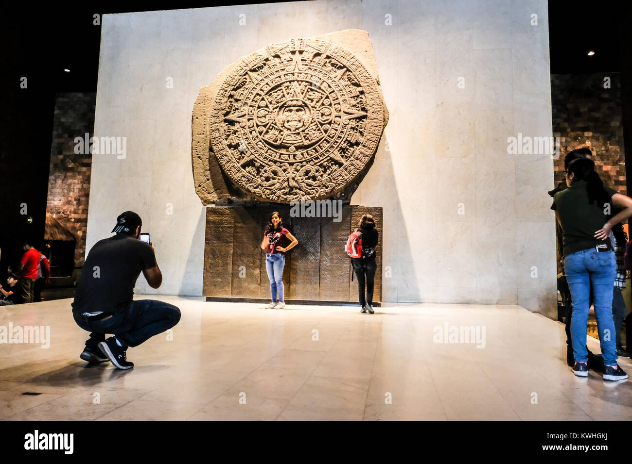 Tourist posing in front of the Sun Stone at the National Museum of Anthropology of Mexico Stock Photo