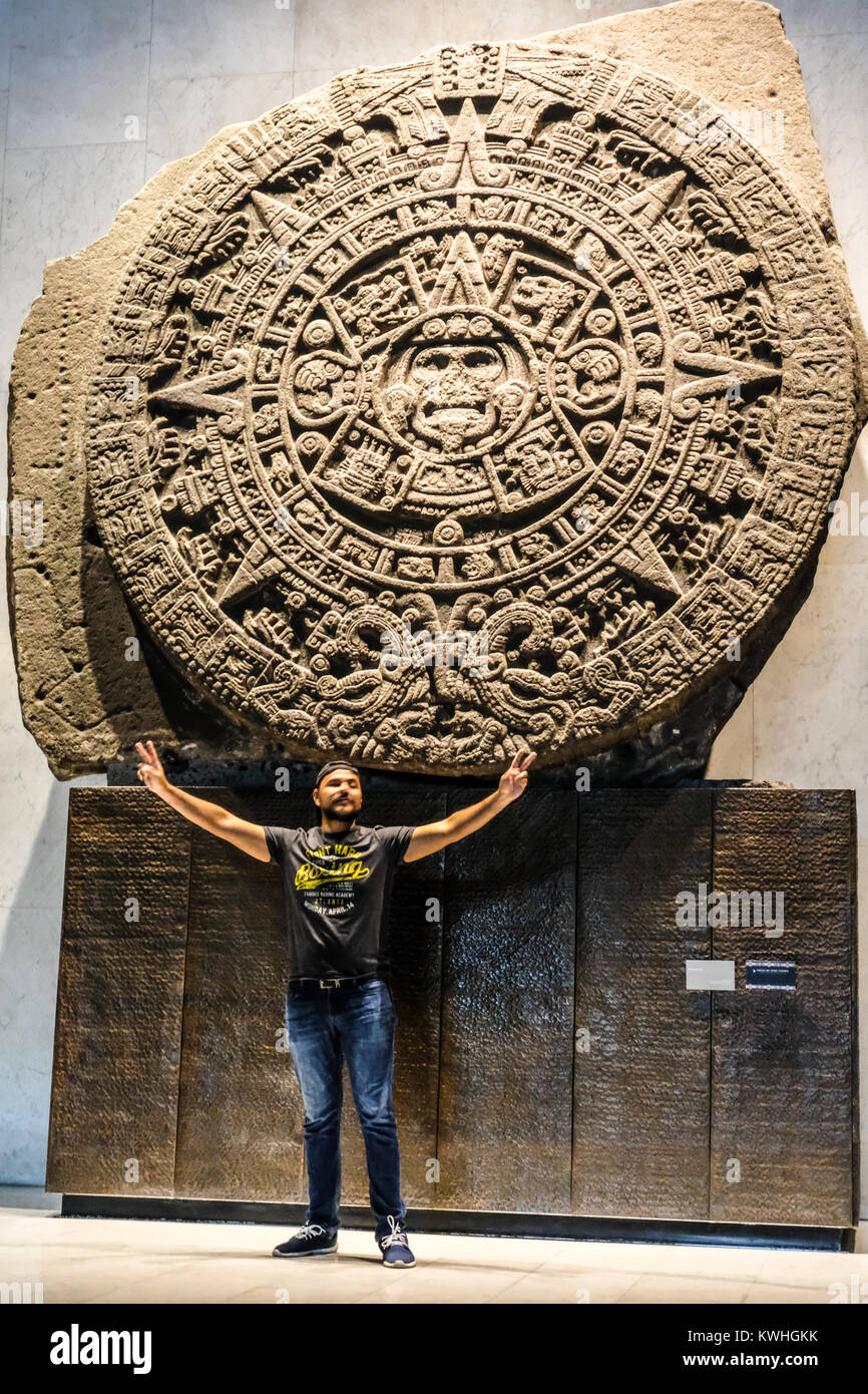 Tourist posing in front of the Sun Stone at the National Museum of Anthropology of Mexico - Stock Image