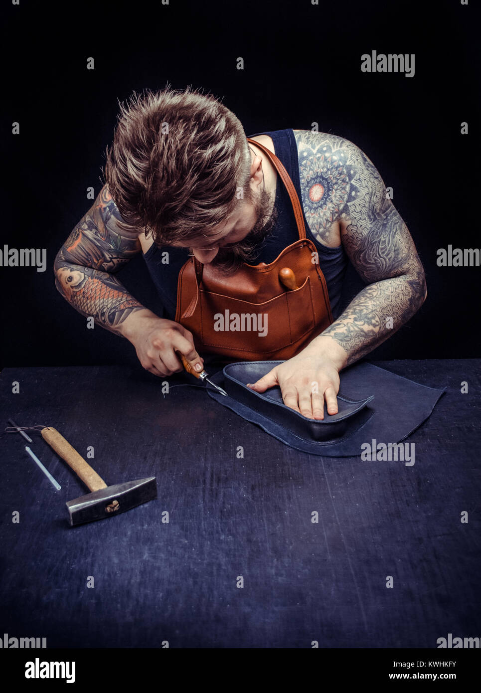 Leather Artist producing a good product at his place of work - Stock Image