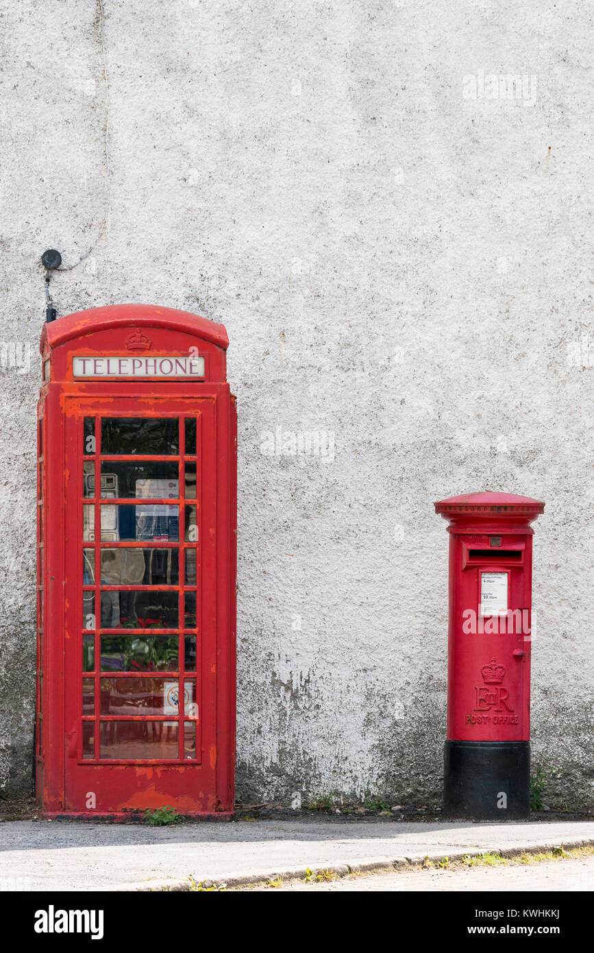 A traditional red phone box and red post box on Lydgate in the Derbyshire village of Eyam, England. - Stock Image
