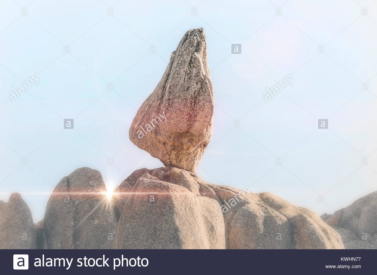 Fog and sunlight scenery at the same time. Strange granitic rock with triangular shape, like a finger pointing to Stock Photo