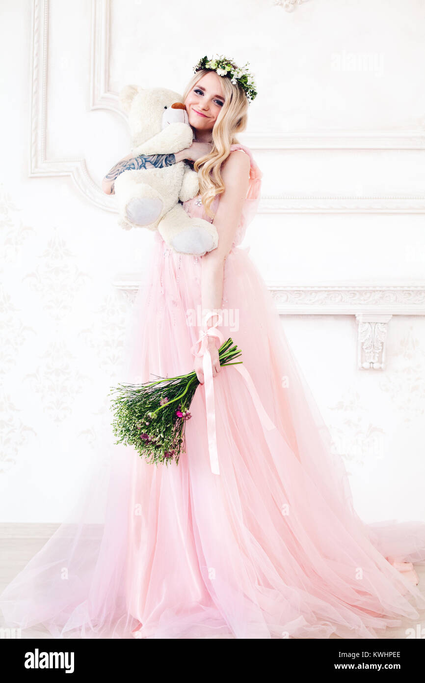 Sweet Woman in Pink Dress holding White Handmade Toy - Stock Image