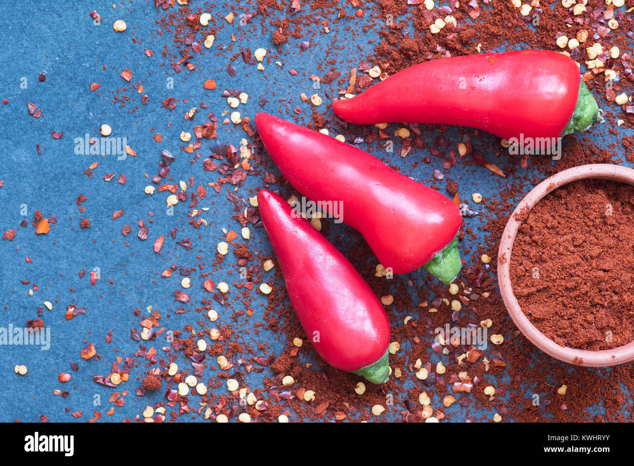 Capsicum. Red chili peppers, Chili powder and dried chili flakes on slate - Stock Image