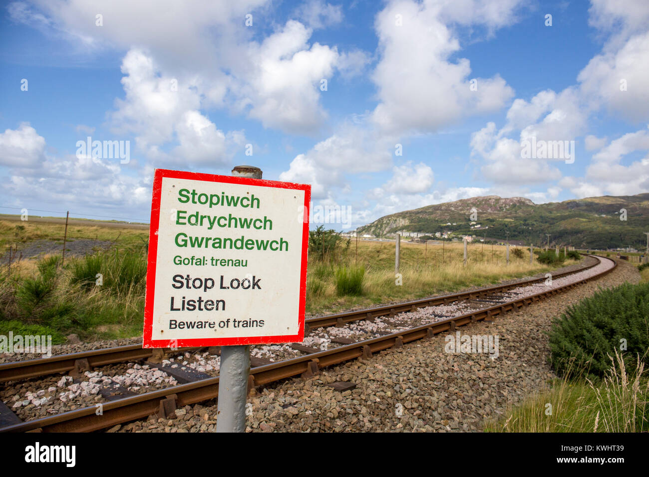 Stop Look Listen warning sign with rail track, Barmouth in distance North Wales UK - Stock Image