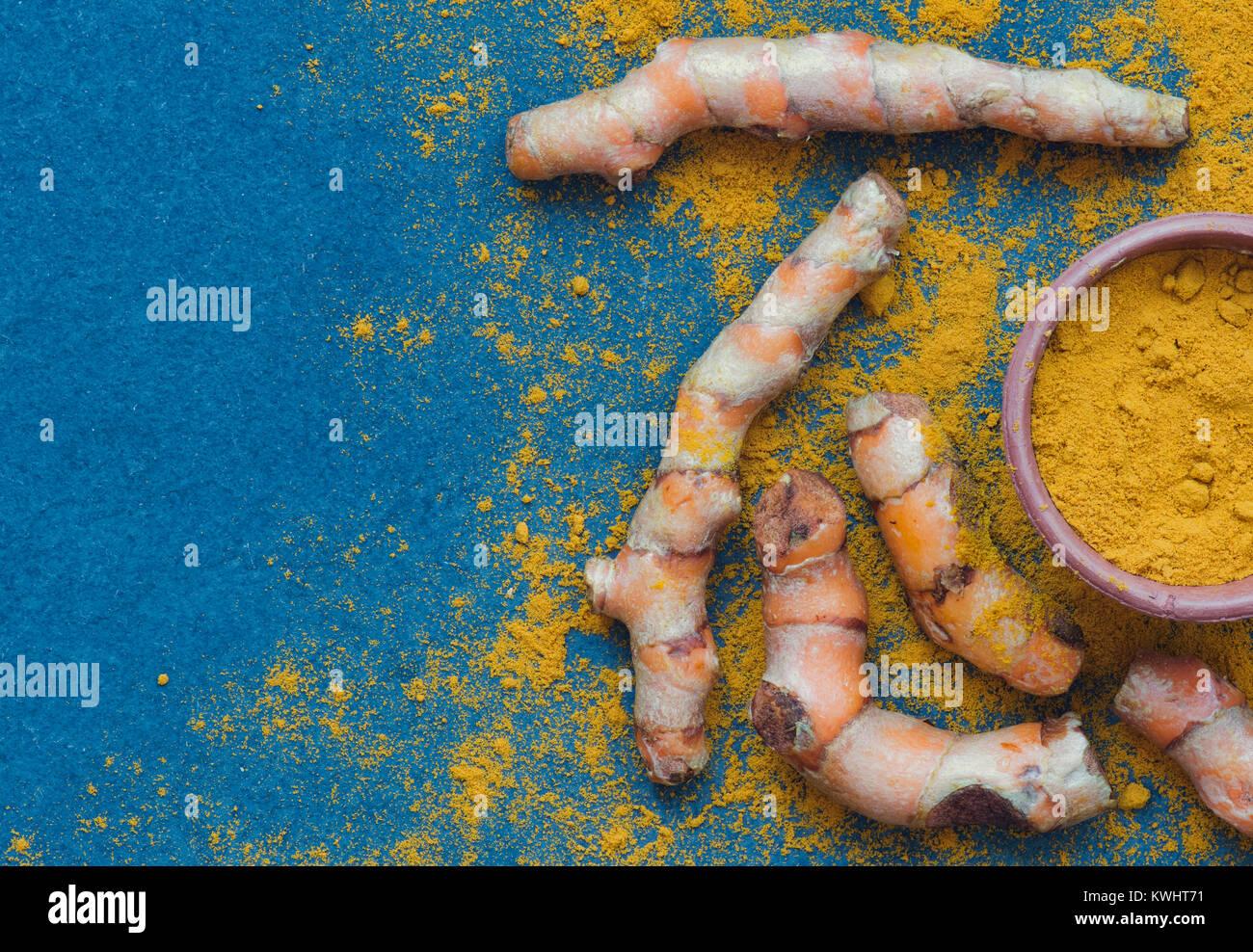 Curcuma longa. Turmeric powder and roots on slate Stock Photo