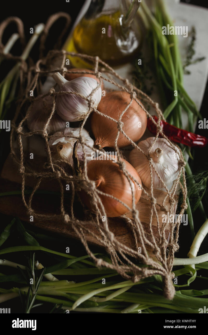 Raw Garlic, onion, dill and parsley for soup for dinner on the wooden table background. Rustic food styling. Natural - Stock Image