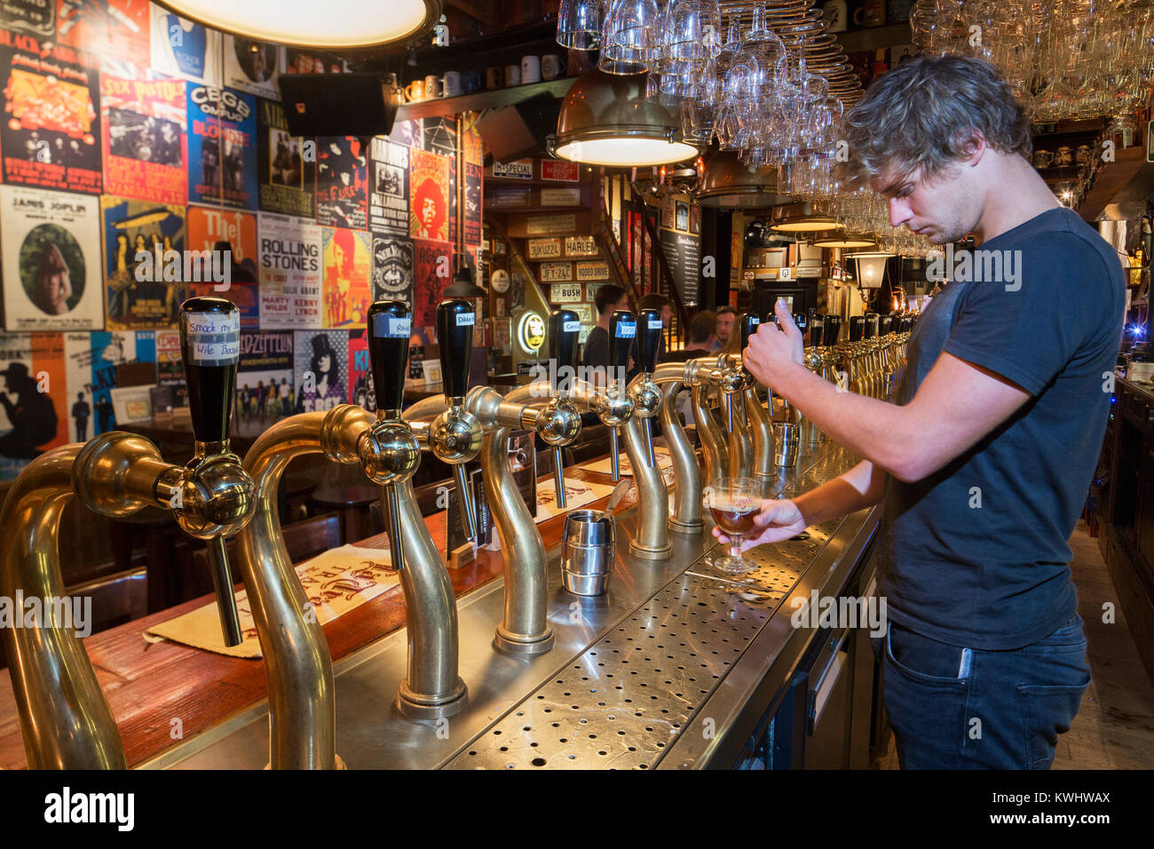 Bartender drawing Belgian draught beer in glass in the Flemish café Rock Circus in the city Ghent, East Flanders, - Stock Image