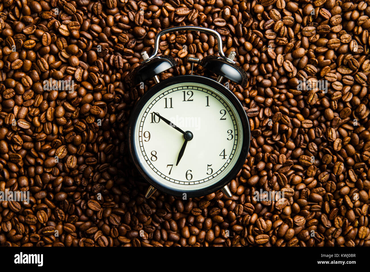 Vintage alarm clock and coffee beans. Top view. - Stock Image