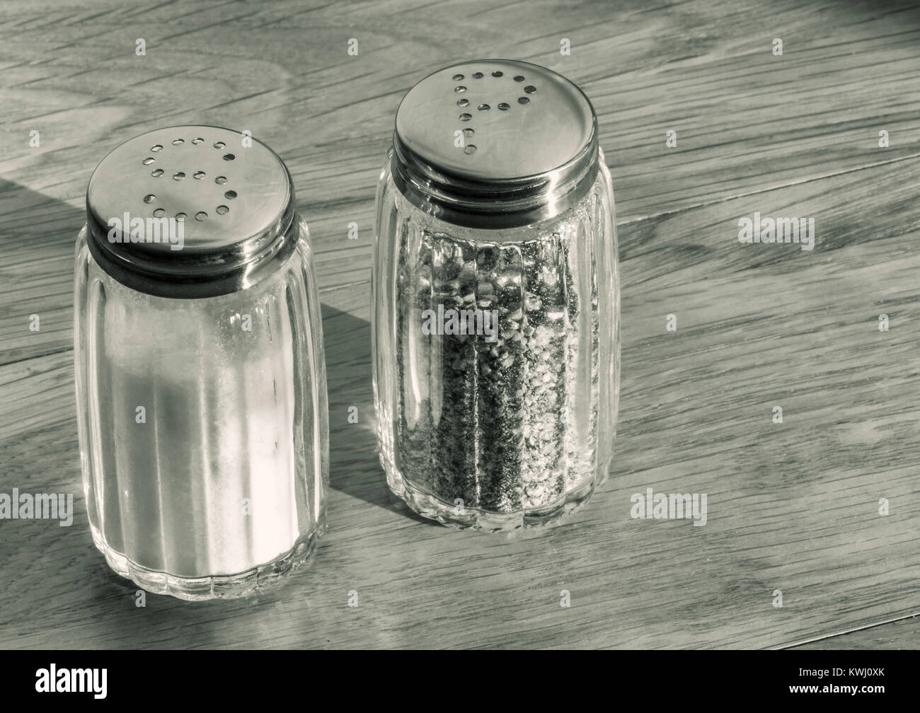 Close up of glass salt and pepper shakers or salt and pepper pots on a wooden table . - Stock Image