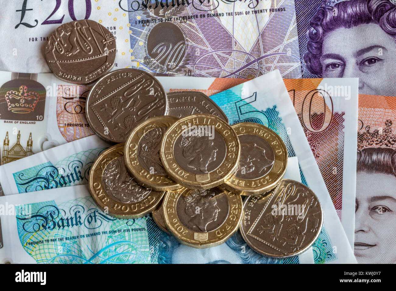 Close up of British currency , £10 pound notes £20 note and £1 coins and other assorted change. - Stock Image