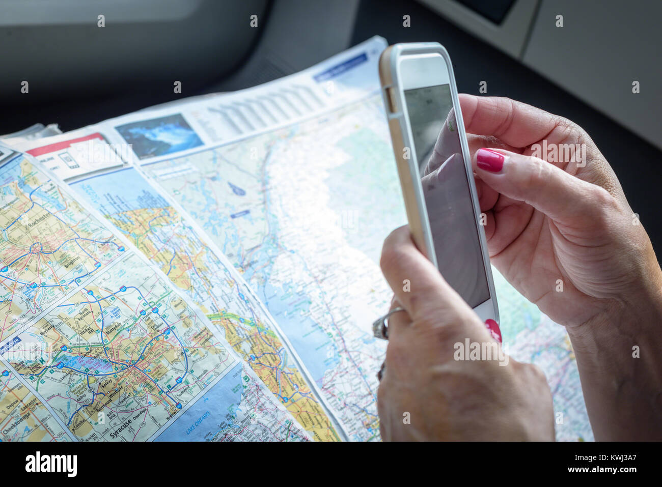 woman holding a smartphone and a paper map getting directions - Stock Image