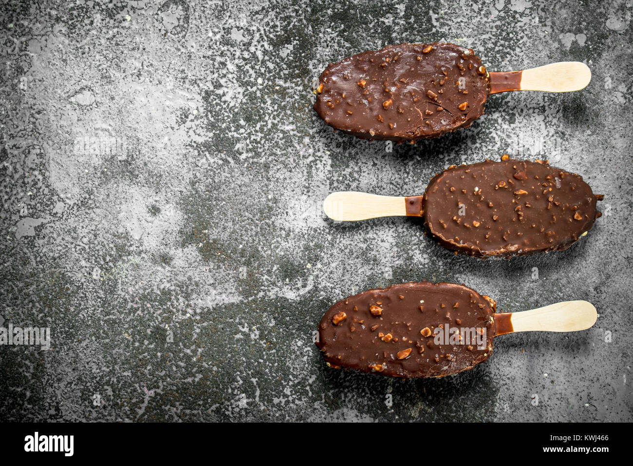 Fresh ice cream on a stick in chocolate with nuts. On a rustic background. Stock Photo
