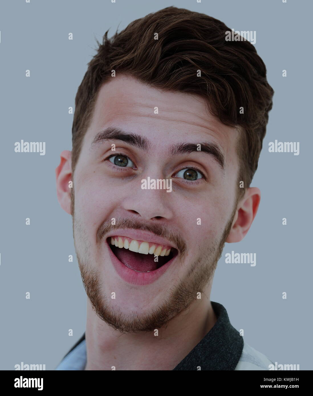 Close-up portrait of attractive young man on gray background - Stock Image