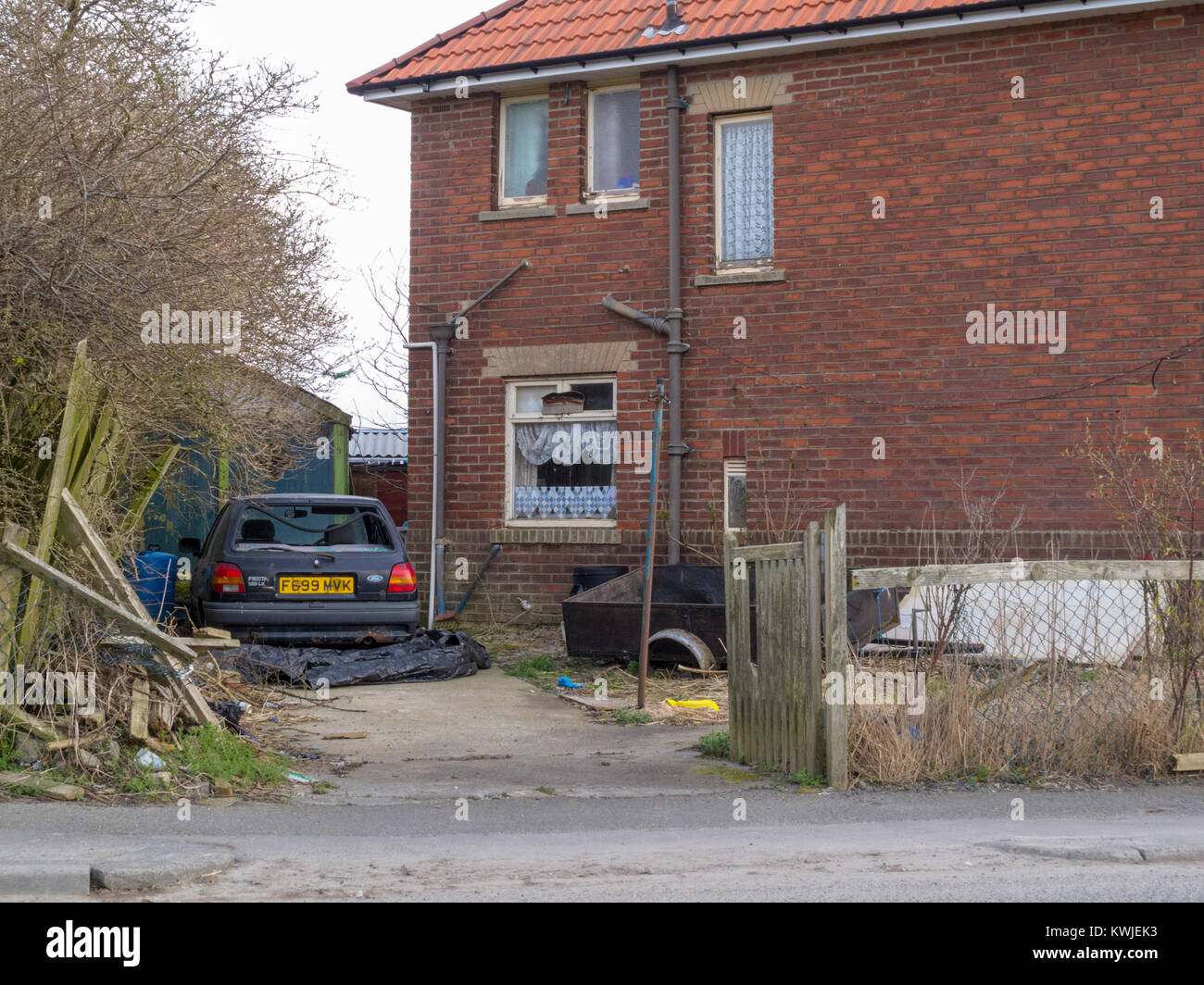 Old Ford Fiesta car with broken windows outside a brick council house in Consett, County Durham, UK, - Stock Image