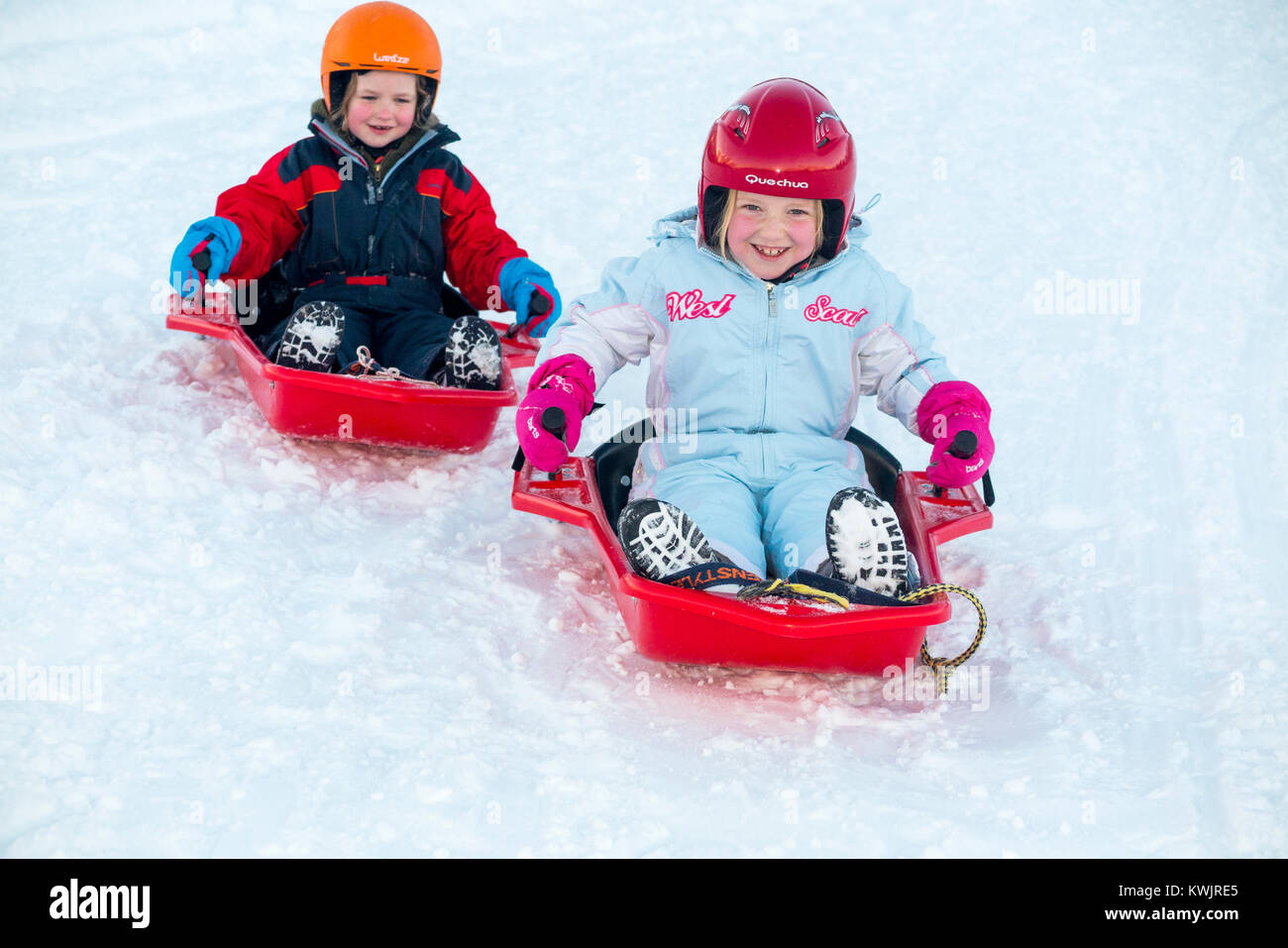 Girls, sisters, aged five, and seven years old, and and wearing ski helmets for safety, enjoy sledging on deep fresh - Stock Image