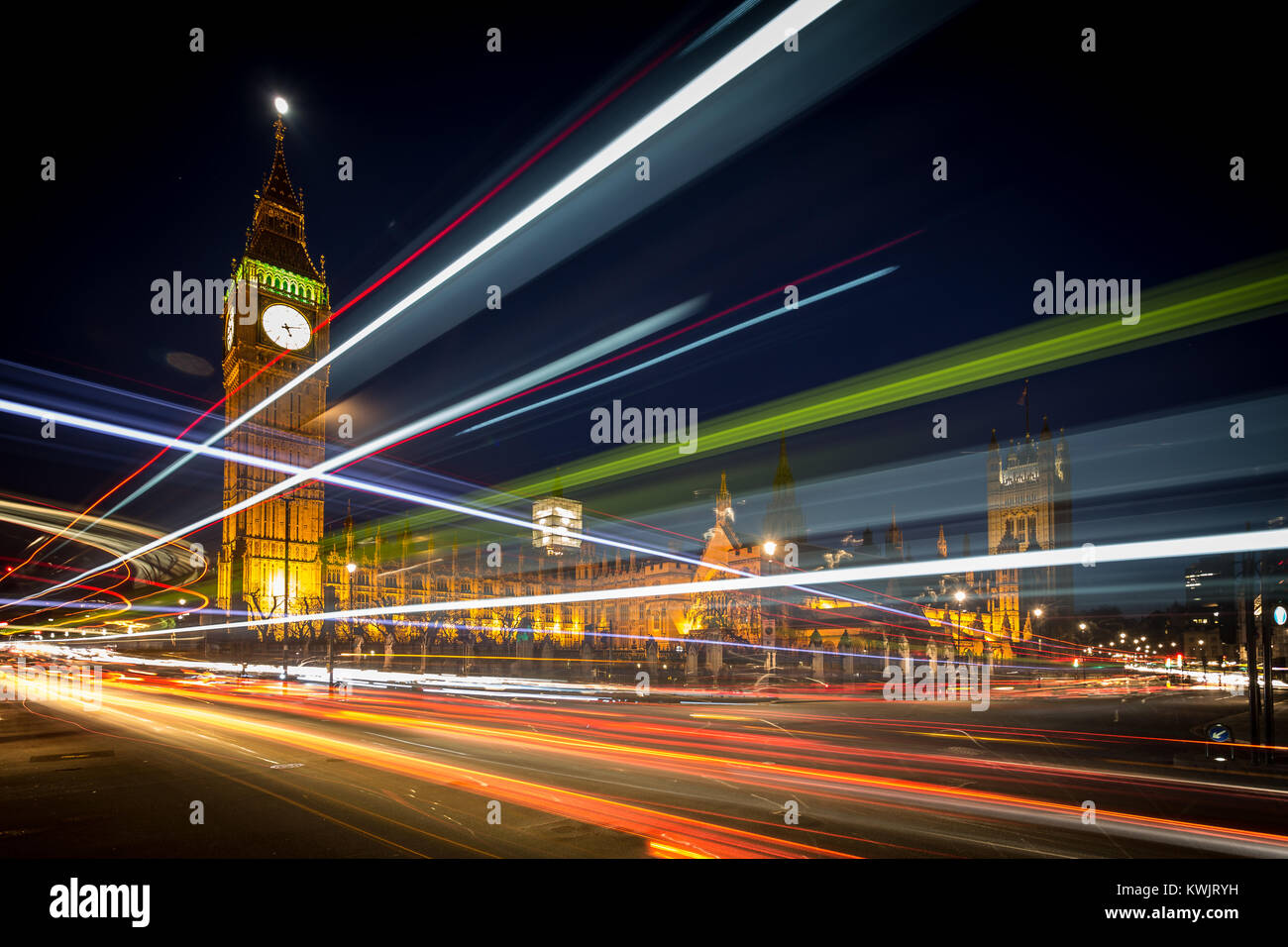 Streaks of light from moving vehicles pass in front of The Houses of Parliament seen from Westminster Sq at dusk - Stock Image