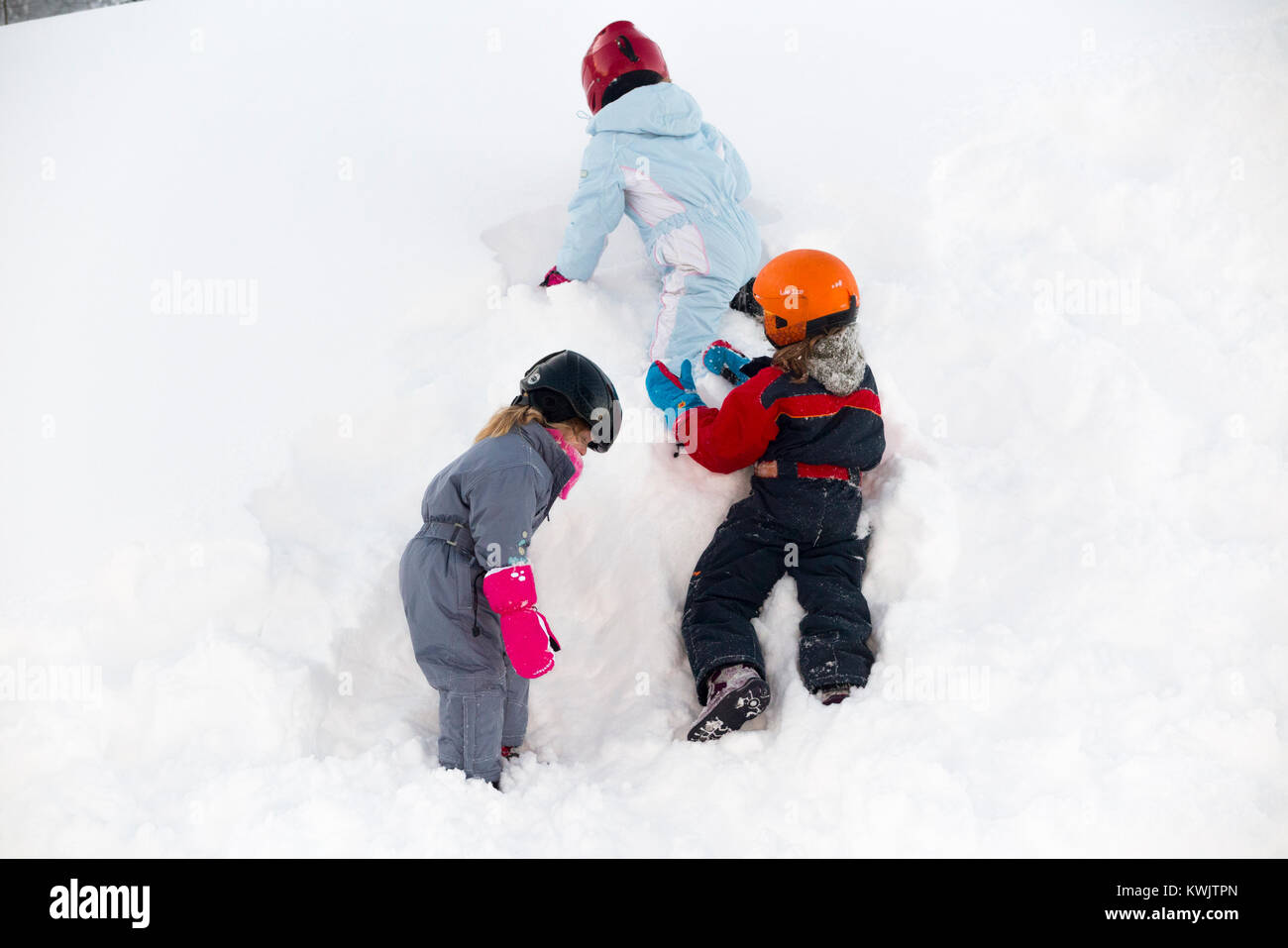 Child / children / kid / kids / three sisters aged 35 and seven years old climb a wall of snow which has drifted - Stock Image