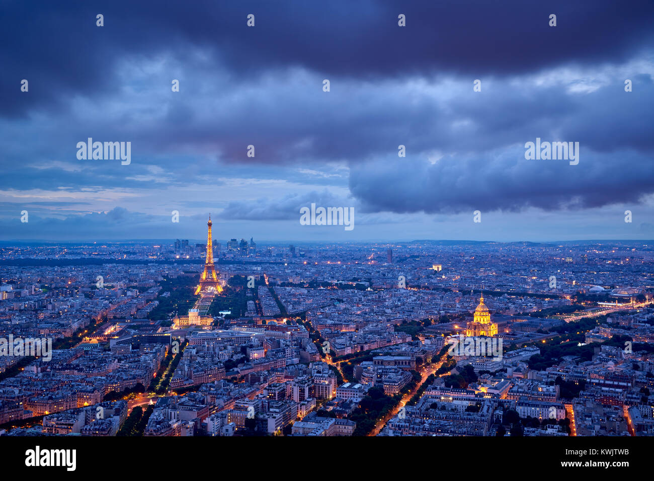Aerial view of Paris rooftops and monuments (illuminated Eiffel Tower and Les Invalides) at twilight. 16th and 7th - Stock Image