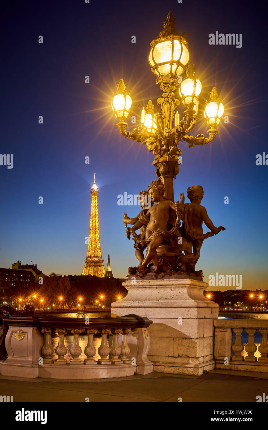 Pont Alexandre III Bridge candelabra style lamp post with the illuminated Eiffel Tower. 8th Arrondissement, Right - Stock Image