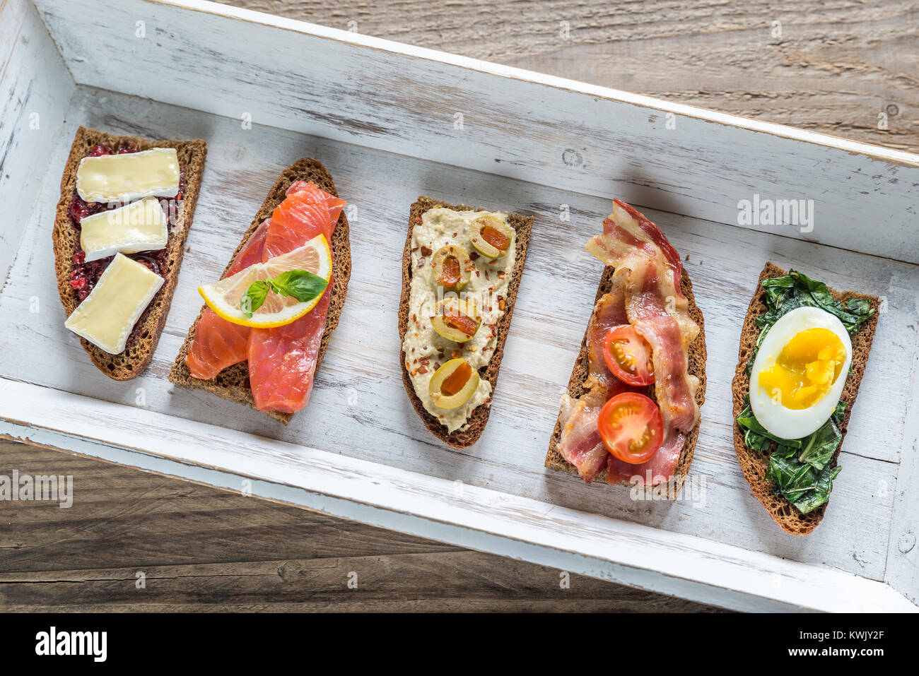 Bruschetta with different toppings on the wooden tray - Stock Image