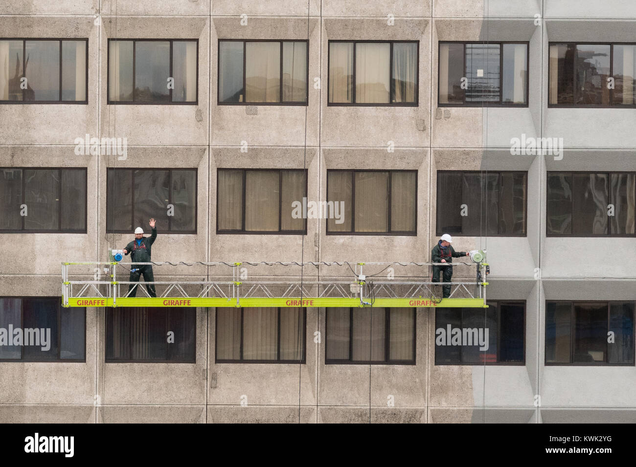 two workers on a suspended access platform renovating the Salvesen Tower office building in Aberdeen, Scotland, - Stock Image