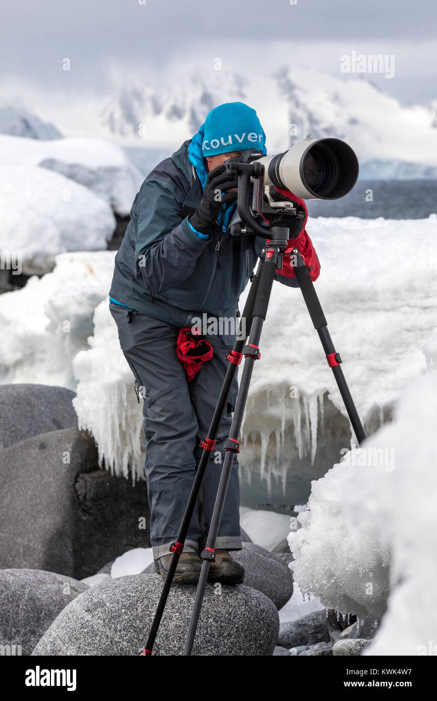 Photographer with huge telephoto lens capturing wildlife; Half Moon Island; Antarctica Stock Photo