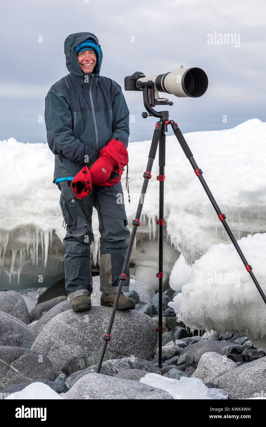 Photographer with huge telephoto lens capturing wildlife; Half Moon Island; Antarctica - Stock Image