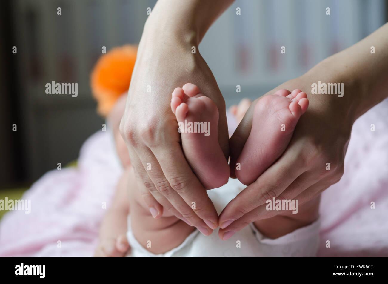 Baby feet in mother hands.baby is sleeping - Stock Image