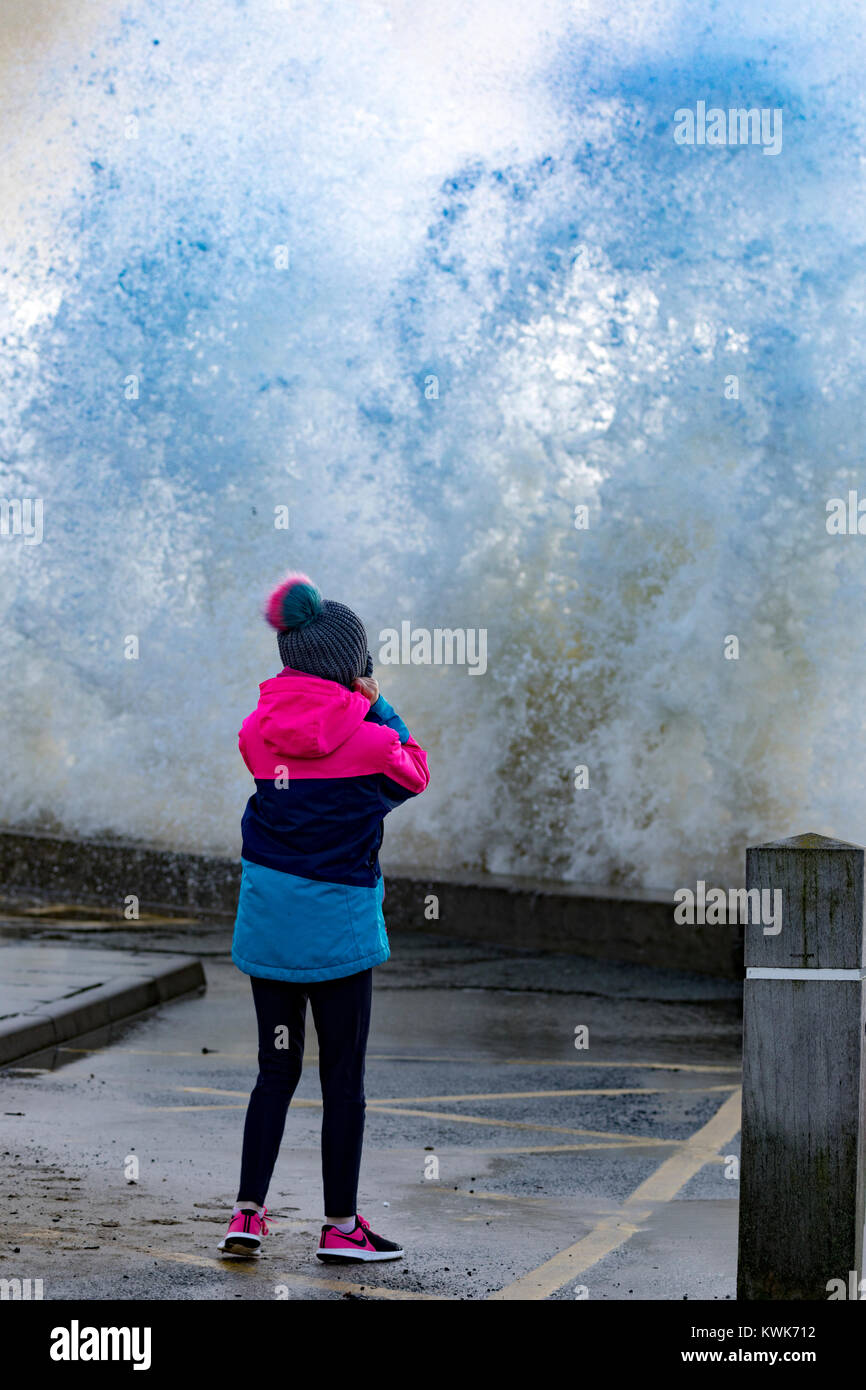 A young girl covering her ears from the noise of the crashing waves at Trearddur Bay on the Isle of Anglesey, Wales, - Stock Image
