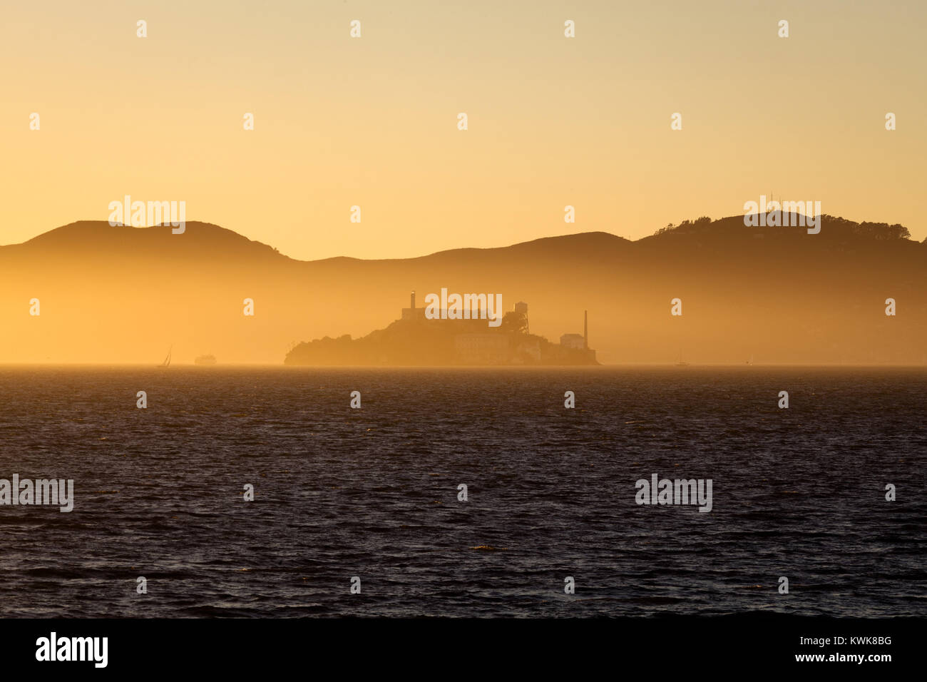 Beautiful view of famous Alcatraz Island illuminated in majestic golden evening light at sunset in summer, San Francisco - Stock Image