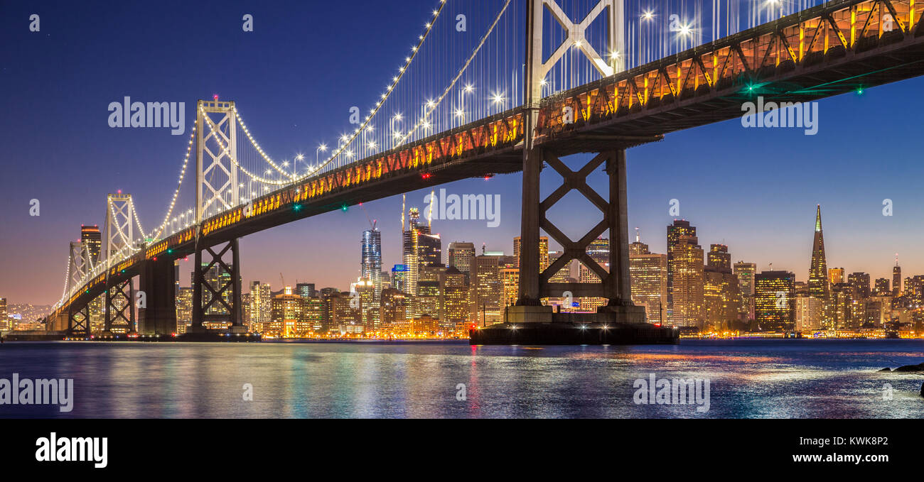Classic panoramic view of famous Oakland Bay Bridge with the skyline of San Francisco illuminated in beautiful twilight - Stock Image