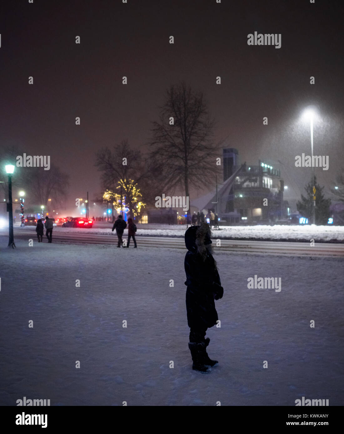 A lady standing in the snow storm trying to gather strength to move on. Bundled up showing what it takes to weather - Stock Image