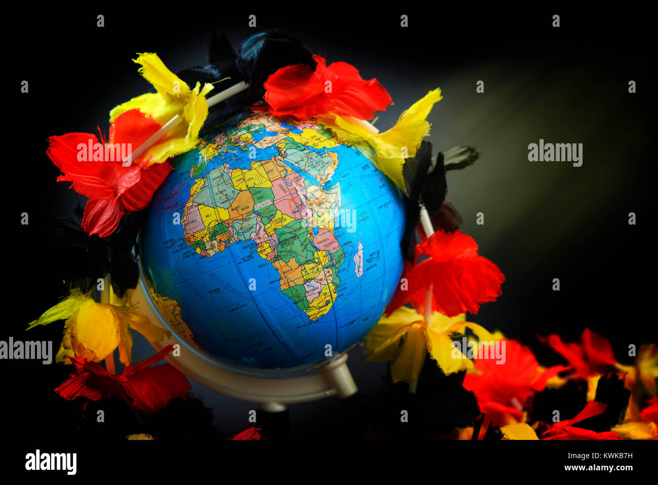 Globe with flower chain in German national colours, symbolic photo refugee's stream to Germany, Globus mit Blumenkette - Stock Image