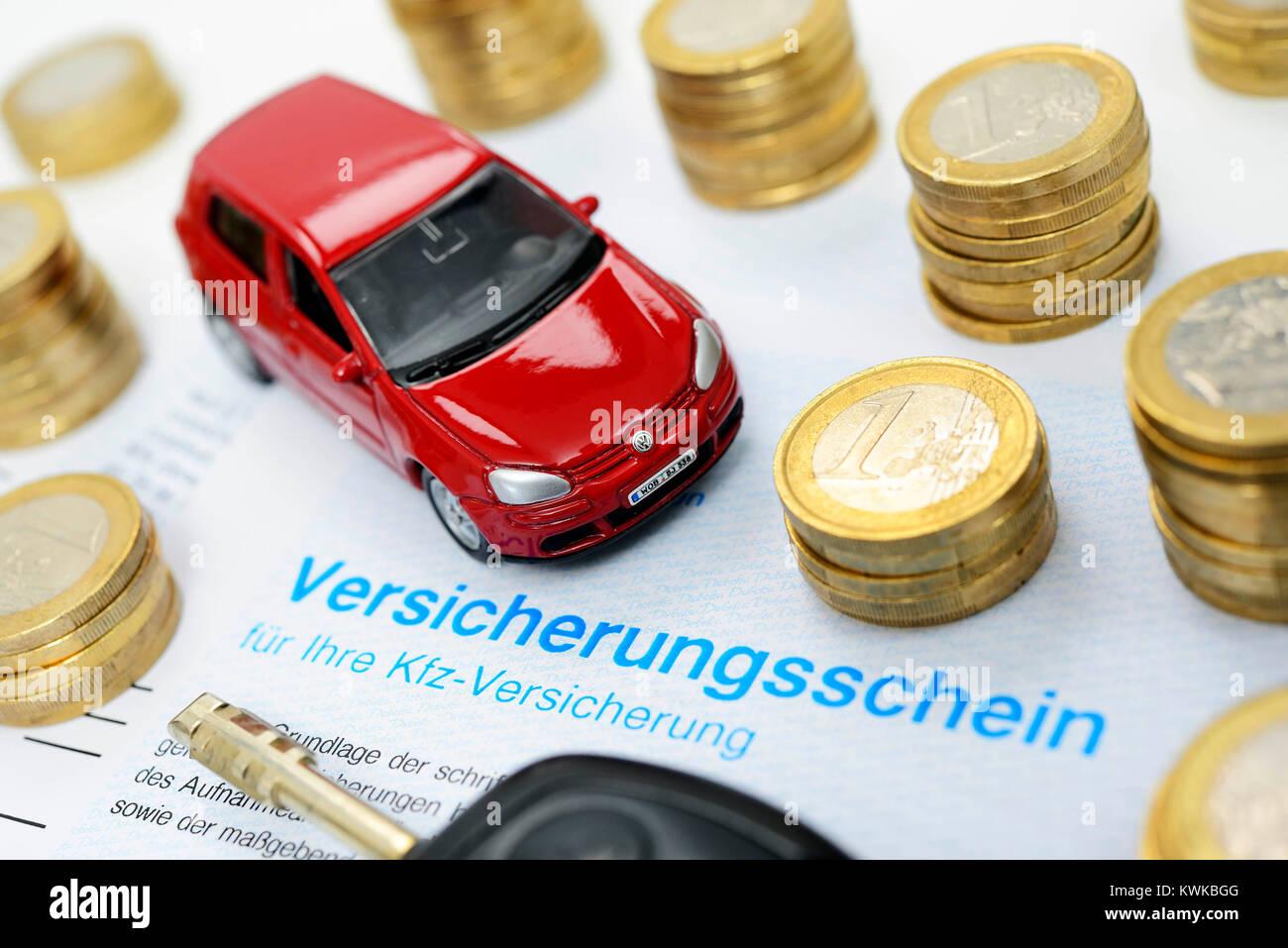 Miniature car and insurance policy, vehicle assurance, Miniaturauto und Versicherungsschein, Kfz-Versicherung - Stock Image