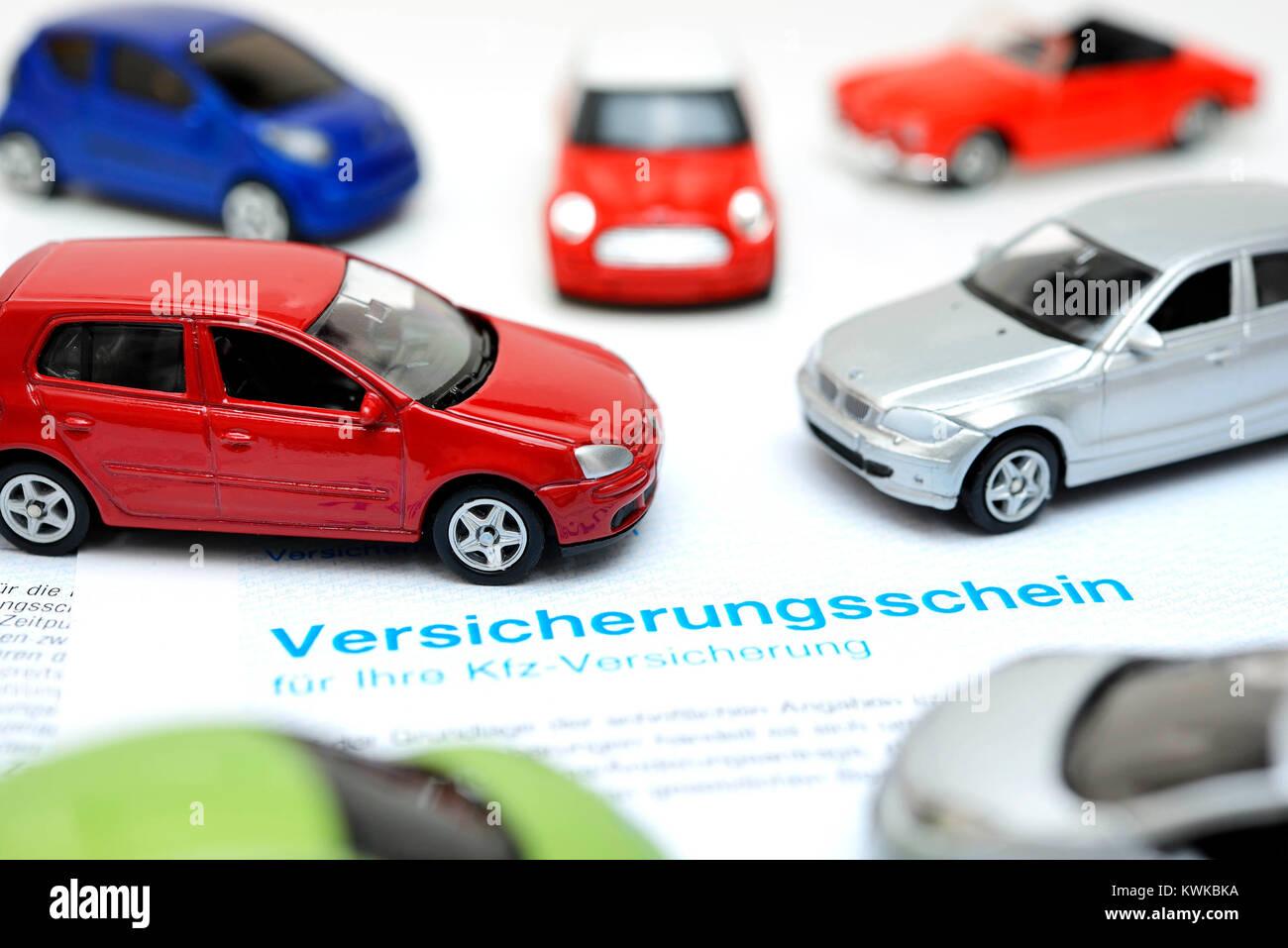Miniature cars and insurance policy, vehicle assurance, Miniaturautos und Versicherungsschein, Kfz-Versicherung - Stock Image