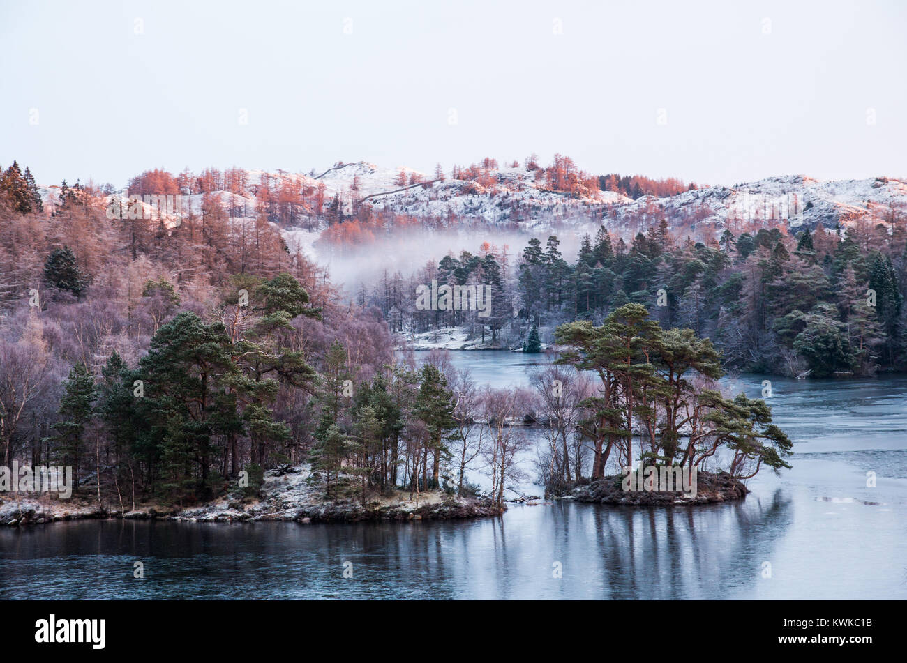 A morning scene on Tarn Hows lake with first sunlight hitting the frost covered hills and mist in low areas. - Stock Image