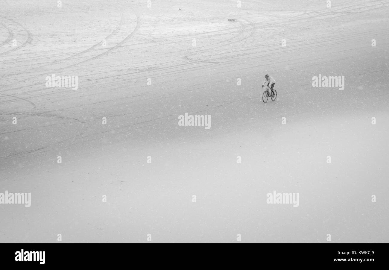 Mtb cycling on his bike against the snowy wind - Stock Image