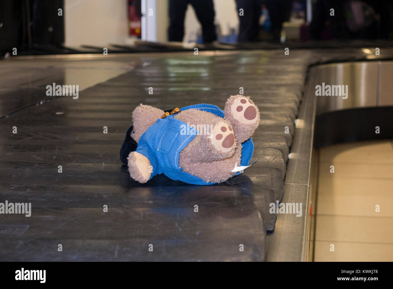 Child's soft toy, a Paddington Bear – possibly lost –  riding luggage claim / baggage reclaim carousel conveyor Stock Photo