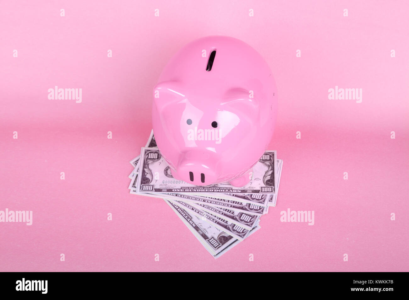Piggy bank on soft pink background with USD dollar money banknotes. - Stock Image