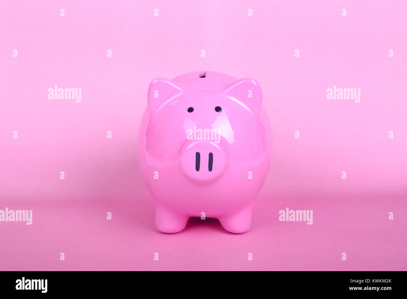 Piggy bank on soft pink background. - Stock Image
