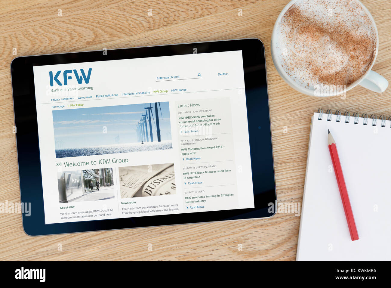 The KfW Group website on an iPad tablet device, resting on a wooden table beside a notepad, pencil and cup of coffee - Stock Image