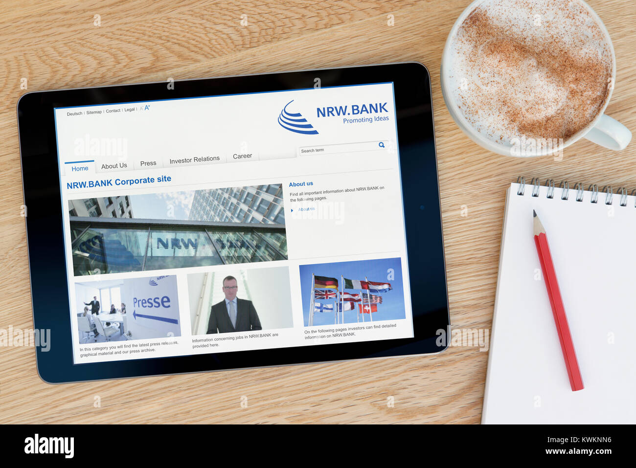 The NRW.BANK website on an iPad tablet device, resting on a wooden table beside a notepad, pencil and cup of coffee - Stock Image