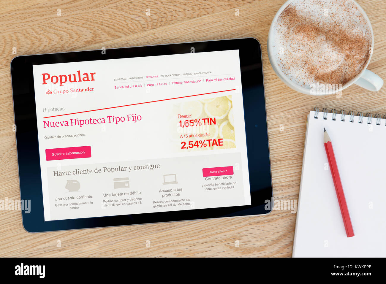The Popular Bank website on an iPad tablet device, resting on a wooden table beside a notepad, pencil and cup of - Stock Image