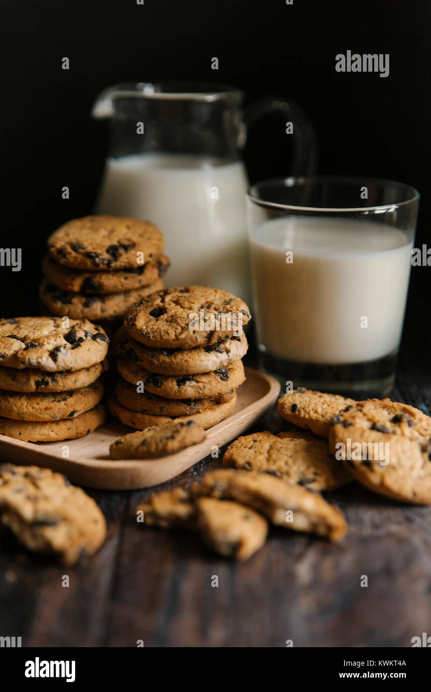 Close-up of cookies and milk on table against black background - Stock Image