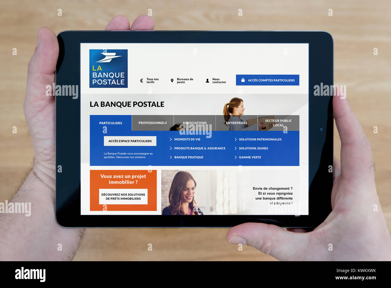 A Man Looks At The La Banque Postale Website On His Ipad Tablet