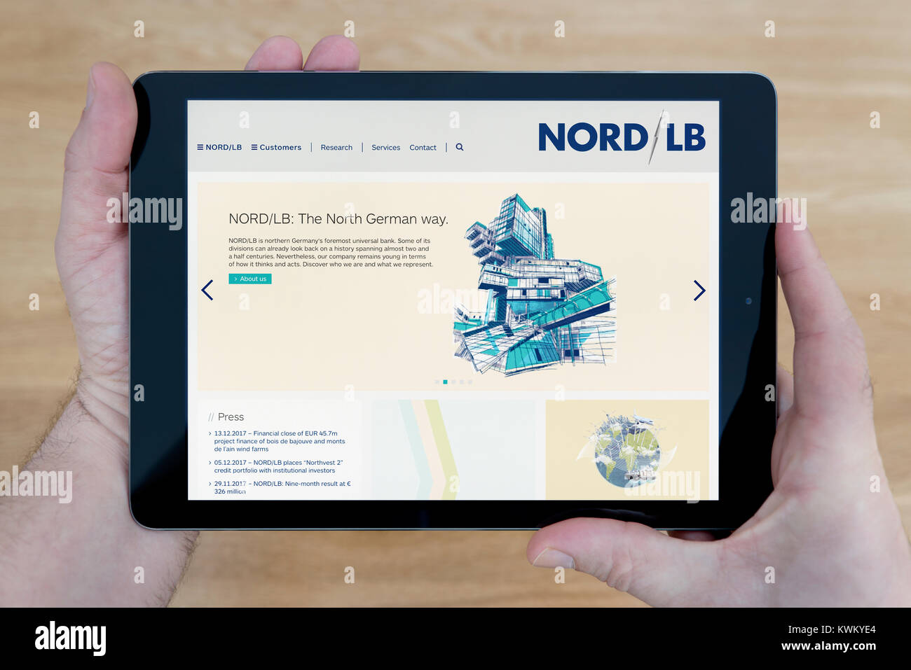 A man looks at the NORD/LB (Norddeutsche Landesbank) website on his iPad tablet device, over a wooden table top - Stock Image